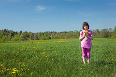 Girl with a bouquet of dandelions. Standing in the meadow Stock Photo