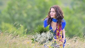 Girl with bouquet  in field Stock Photo