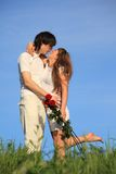 Girl with bouquet kisses guy against sky Stock Photo