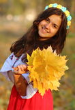 Girl with a bouquet of leaves. Girl with a bunch of leaves in the hands of royalty free stock photo