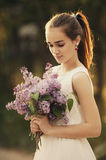 Girl with bouquet of lilac Stock Photos