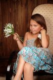 Girl with a bouquet lilies of the valley in chair Royalty Free Stock Photo