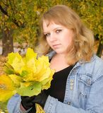 Girl with a bouquet of maple leaves Royalty Free Stock Photos