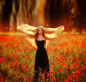 Girl with a bouquet of poppies in black dress royalty free stock photography