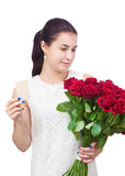 Girl with bouquet of red roses and card in hand. Stock Images