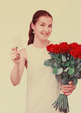 Girl with bouquet of red roses and card in hand. Royalty Free Stock Photo