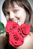Girl a bouquet of roses. Beautiful young woman with a bouquet of red roses Royalty Free Stock Photography