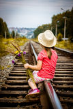 Girl with a bouquet sitting on the rails Stock Photography