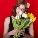 Girl with a bouquet of spring flowers on a red background Royalty Free Stock Photo
