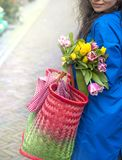 Girl with a bouquet of spring tulips in pink. In a blue raincoat and yellow boots on the street in Europe. Happy woman. Smile on royalty free stock photos