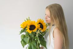 Girl with a bouquet of sunflowers stock photo