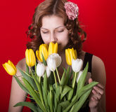 Girl with a bouquet of tulips on red background Royalty Free Stock Image