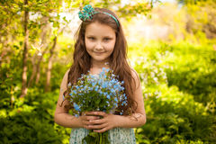 Girl with a bouquet of wild blue flowers Royalty Free Stock Images