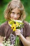 Girl with a bouquet of wild flowers. Young girl holding a fresh bouquet of fresh wild flowers Royalty Free Stock Photography