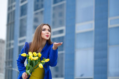 Girl with bouquet of yellow tulips. Young attractive girl in a blue coat and yellow dress holding a bouquet of yellow tulips. Spring is coming to town. She sends Royalty Free Stock Image