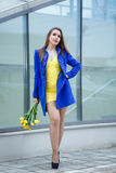 Girl with bouquet of yellow tulips. Young attractive girl in a blue coat and yellow dress holding a bouquet of yellow tulips. Spring is coming to town. She is Royalty Free Stock Image