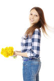 Girl with bouquet yellow wildflowers. Teenage Girl in jeans and a plaid shirt, holding a bouquet of dandelions. Stock Images