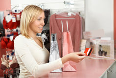 The girl in a boutique. The blonde with packages in an underwear boutique holds a credit card in a hand Stock Images