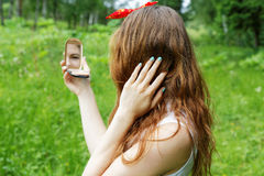 Girl with a bow on her head looking into the mirror Stock Images