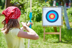 Girl with bow shooting to sport aim Stock Photos