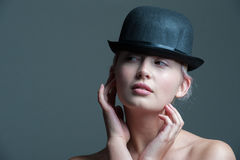 53e8a0e2ebf Girl in bowler hat. Young lady posing in a black bowler hat royalty free  stock