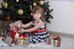 Girl with a box with a gift near the Christmas tree Stock Images