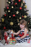 Girl with a box with a gift near the Christmas tree Stock Photography