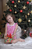 Girl with a box with a gift near the Christmas tree Stock Photo