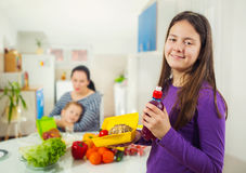 Girl with a box for a snack in the kitchen Stock Photos