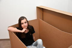 Girl in a box. Teenager girl sitting in an empty moving box stock photo