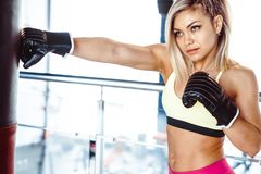 Girl boxer beats the punching bag. Fighter girl punching actively. motion long hair royalty free stock photos