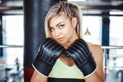 Girl boxer beats the punching bag. Fighter girl punching actively. motion long hair royalty free stock images