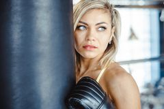 Girl boxer beats the punching bag. Fighter girl punching actively. motion long hair stock image