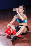 The girl boxer sitting on a floor in a hall Royalty Free Stock Photos