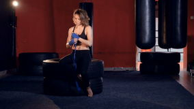 The girl boxer is sitting on the wheels adjusting the bandages. 4K. The girl boxer is sitting on the wheels adjusting the bandages stock video footage