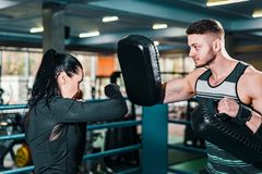 Girl boxer trains. coach holds boxing focus pads. athlete practicing shots in the gym. stock image