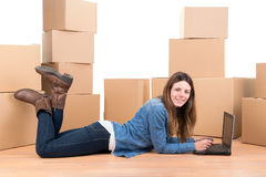 Girl with boxes. Beautiful girl with laptop and cardboard boxes unpacking in new home Stock Images