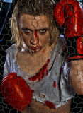 Girl with boxing gloves. Blonde girl wearing boxing gloves with bloody face Royalty Free Stock Photo