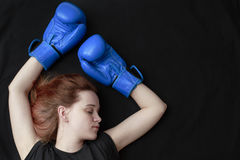 A girl in boxing gloves lies on the floor Stock Photography