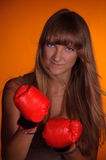 Girl in boxing gloves. The girl in boxing gloves preparing to strike Stock Photos