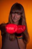 Girl in boxing gloves. The girl in boxing gloves preparing to strike Stock Photo
