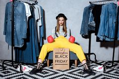 girl in boxing gloves with shopping bag with black friday sign and clothes royalty free stock images