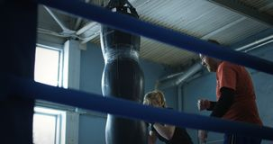 Girl boxing punchbag with trainer. View through boxing ring from below of serious sportive girl punching bag while training with boxing coach on ring stock video footage
