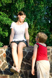 Girl and boy 3. Children in park. The enamoured boy looks at the girl. The girl looks at the boy and smiles Stock Images