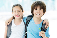 Girl and boy with backpacks Stock Images