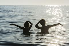 Girl and boy bathing and dancing in the sea in summer stock photo