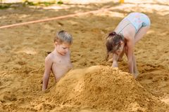 Girl and boy in bathing suits bury their feet in the sand on the beach in summer. Funny girl and boy in bathing suits bury their feet in the sand on the beach in stock images