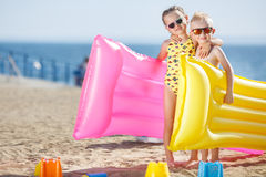 Girl and boy on the beach with inflatable mattress Stock Images