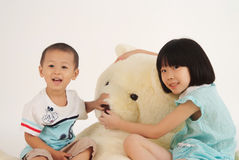 Girl and boy with bear toy royalty free stock photography
