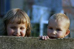 Girl and boy behind the fence. Small little boy and girls with golden hair behind the fence Stock Photos